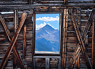Mount Wilson viewed through the window of an old mining structure in the ghost town of Alta, Colorado.