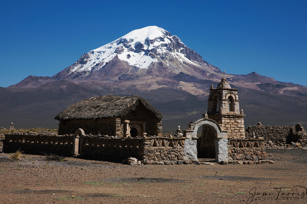 An old Andean church  in front of volcanos Parinacota and Sajama on the Altiplano , Bolivia, South America