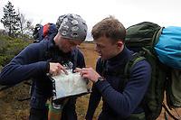 To menn med ryggsekker studerer kart og terreng, two men with backpacks study the map and terrain