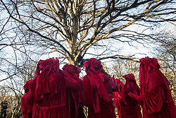 Harefield, UK. 18 January, 2020. The Red Rebel Brigade shows support for earth protectors in trees at the Colne Valley wildlife protection camp which was today reoccupied by activists from Extinction Rebellion, Stop HS2 and Save the Colne Valley on the second day of a three-day 'Stand for the Trees' protest in the Colne Valley timed to coincide with tree felling work by HS2. Bailiffs acting for HS2 had evicted all but two activists from the camp the previous week. 108 ancient woodlands are set to be destroyed by the high-speed rail link.
