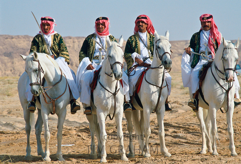 Bedouin men riding horses in the desert inSaudi Arabia.