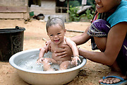 A young baby boy and his mother enjoy bathtime outside their home in the Khmu village of Ban Kengdeung, Phongsaly province, Lao PDR. The remote and roadless village of Ban Kengdeung is situated along the Nam Ou river (a tributary of the Mekong) and will be relocated due to the construction of the Nam Ou Cascade Hydropower Project Dam 5. The Nam Ou river connects small riverside villages and provides the rural population with food for fishing. But this river and others like it, that are the lifeline of rural communities and local economies are being blocked, diverted and decimated by dams. The Lao government hopes to transform the country into 'the battery of Southeast Asia' by exporting the power to Thailand and Vietnam.