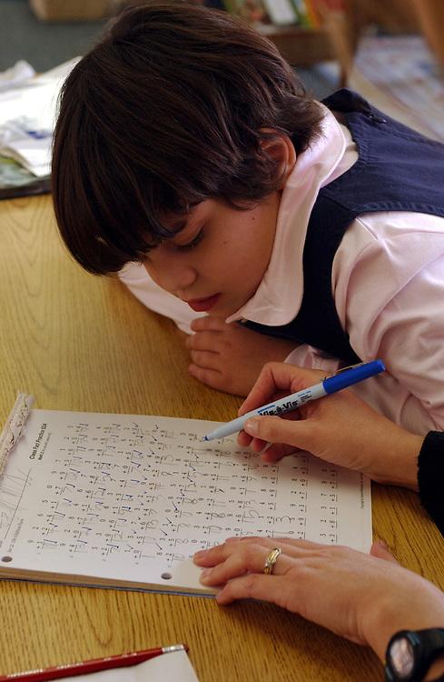 Grading paper in math at third grade girls-only school working on math problems all-girls school, Austin, TX.  <br /> ©Bob Daemmrich