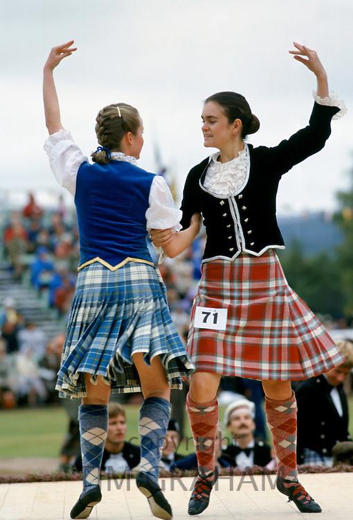 Scottish girls in tartan kilts dancing traditional dance at the Braemar Royal Highland Gathering, the Braemar Games in Scotland