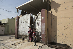 November 11, 2016 - Mosul, Nineveh, Iraq - 11/11/2016. Mosul, Iraq. Two Iraqi children stand in front of their home's bullet riddled gate in Mosul's Al Intisar district on the south east of the city. The Al Intisar district was taken four days ago by Iraqi Security Forces (ISF) and, despite its proximity to ongoing fighting between ISF and ISIS militants, many residents still live in the settlement without regular power and water and with dwindling food supplies...The battle to retake Mosul, which fell June 2014, started on the 16th of October 2016 with Iraqi Security Forces eventually reaching the city on the 1st of November. Since then elements of the Iraq Army and Police have succeeded in pushing into the city and retaking several neighbourhoods allowing civilians living there to be evacuated - though many more remain trapped within Mosul. (Credit Image: © Matt Cetti-Roberts via ZUMA Wire)