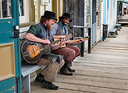 Actors in period costume play stringed instruments at Barkerville Historic Town & Park, British Columbia, Canada. Historically the main town of the Cariboo Gold Rush, Barkerville is now the largest living-history museum in Western North America. The town was named after Billy Barker from Cambridgeshire, England, who struck gold here in 1861, and his claim became the richest and the most famous. This National Historic Site nestles in the Cariboo Mountains at elevation 1200m (4000ft), at the end of BC Highway 26, 80 kilometres (50 mi) east of Quesnel. Gold here was first discovered at Hills Bar in 1858, followed by other strikes in 1859 and 1860. Wide publication of these discoveries in 1861 began the Cariboo Gold Rush, which reached full swing by 1865 following strikes along Williams Creek. To license this Copyright photo, please inquire at PhotoSeek.com.