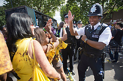 © London News Pictures. 26/08/2012. London, UK. A policeman give high five to performers taking part in day one of the Notting Hill Carnival in West London on August 26, 2012.  The annual carnival, which is the largest of its kind in Europe, is expected to attract around 1 million people. Photo credit : Ben Cawthra/LNP