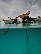 Fishing and hunting coral fish with Dido, from his dug-out canoe. Off Mantabuan island.