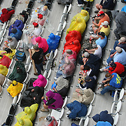 Rain forces fans on the front stretch to put on their rain gear during the 56th Annual NASCAR Daytona 500 practice session at Daytona International Speedway on Saturday, February 22, 2014 in Daytona Beach, Florida.  (AP Photo/Alex Menendez)