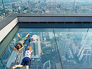 """27 DECEMBER 2018 - BANGKOK, THAILAND:  Children on the """"glass tray,"""" a glass overlook that sticks out over the south edge of the Maha Nakhon Tower. The MahaNakhon Skywalk, at the top of the King Power Maha Nakhon Tower, is 1,030 feet (314 meters) above street level. It is the tallest building and highest vantage point in Bangkok. The skywalk opened in November and has been drawing large crowds.    PHOTO BY JACK KURTZ"""