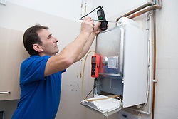 Gas man testing a boiler using special equipment,