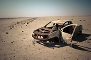 Rusted old car on the side of the very remote road through the Namib desert, Namibia, Africa