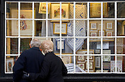 Elderly couple look in the window of a haberdashery shop,  Burford, Oxfordshire, UK