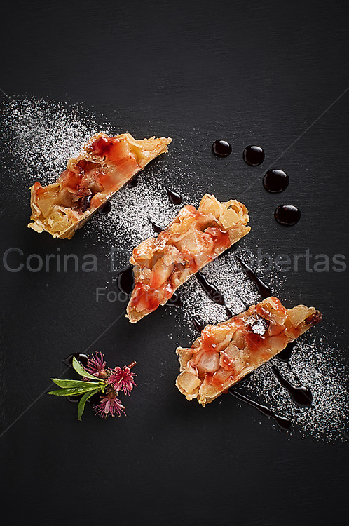 Three slices of apple strudel on a slate plate decorated with icing sugar and caramel sauce.