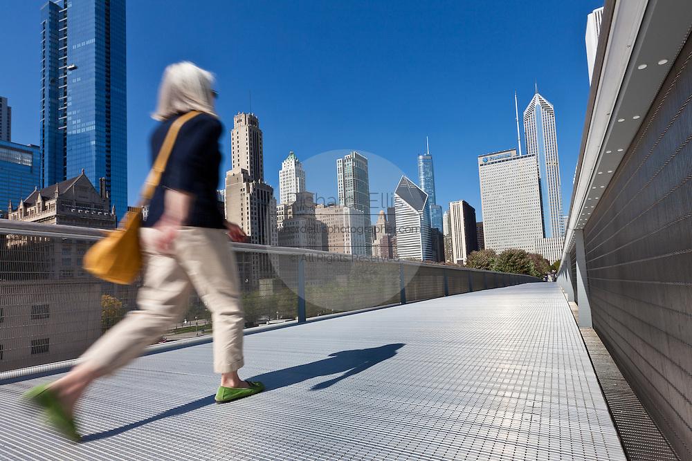 A pedestrian walks the Nichols Bridgeway with the Skyline of Chicago from Millennium Park in Chicago, IL, USA.