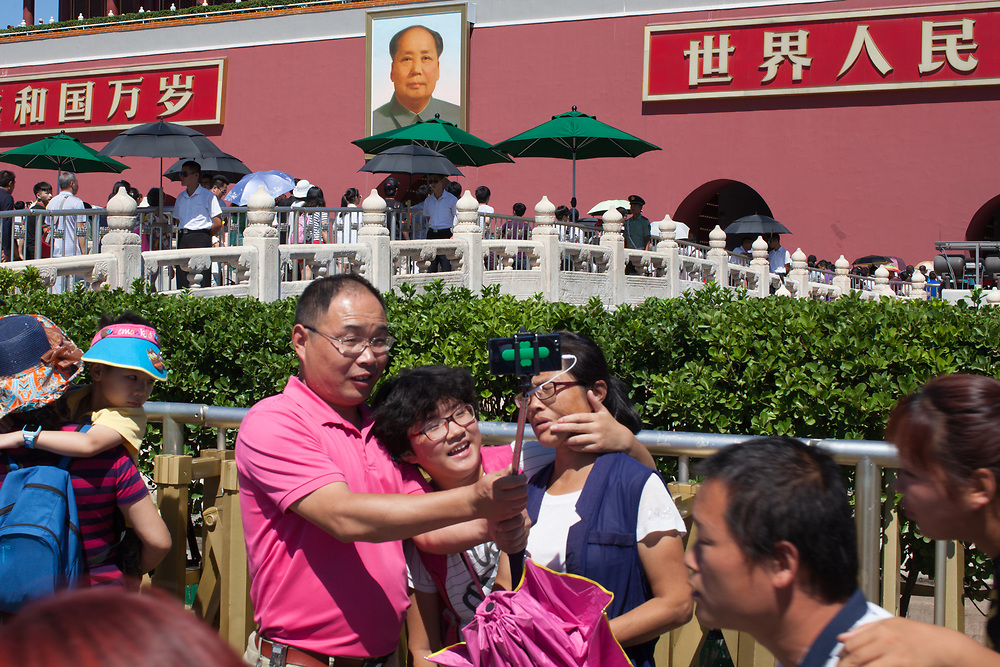 Chinese tourists pose for selfies in front of Chairman Mao's portrait on Tianenmen Square, Beijing, China