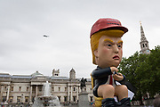 On US President Donald Trump's second day of a controversial three-day state visit to the UK, the Presidential Helicopter Marine One flies over a Trump effigy tweeting while sitting on a golden toilet as protesters voice their opposition to the 45th American President, in Trafalgar Square, on 4th June 2019, in London England.