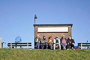 Nederland, Millingen aan de Rijn, 23-2-2019Een groepje oudere mannen, pensionados, zit op een bankje aan de dijk . Ze genieten van het uitzonderlijk mooie weer van deze dagen .Foto: Flip Franssen