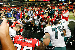 Philadelphia Eagles and Atlanta Falcons come together for a prayer after the NFL game between the Philadelphia Eagles and the Atlanta Falcons on December 6th 2009. The Eagles won 34-7 at The Georgia Dome in Atlanta, Georgia. (Photo By Brian Garfinkel)