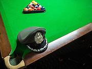 """26 JUNE 2015 - BANGKOK, THAILAND:  A Thai police hat on a pool table at the Foreign Correspondents' Club of Thailand. Human Rights Watch (HRW) was scheduled to launch a new report, """"Persecuting 'Evil Way' Religion: Abuses against Montagnards in Vietnam"""", at the Foreign Correspondents' Club of Thailand (FCCT) in Bangkok Friday morning. The report made no mention of the human rights situation in Thailand. The Thai Ministry of Foreign Affairs (MFA) contacted HRW Thursday afternoon and asked them to cancel the program because it was a """"sensitive"""" matter that could impact on Thai-Vietnam relations. HRW told the MFA that they would go ahead with the report's release. Friday morning, before the report was scheduled to be released, Thai police officers arrived at the FCCT and cancelled the event. Phil Robertson, deputy director of Human Rights Watch's Asia division, said, """"By stepping in to defend a neighboring state's human rights violations against a group of its people and interrupting a scheduled press conference, Thailand's military junta is violating freedom of assembly and demonstrating its contempt for freedom of the press.""""      PHOTO BY JACK KURTZ"""