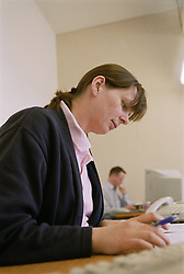 Woman working at desk in translation agency office; translating material,