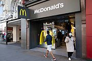 Woman wearing a face mask leaves McDonalds with her McFlurry, which is now closed as a sit down fast food restaurant, but still open for take away orders on Oxford Street, Londons main shopping and retail area normally full of thousands of shoppers and traffic is virtually deserted due to the Coronavirus outbreak on 23rd March 2020 in London, England, United Kingdom. Following government advice most shoppers are staying at home leaving the streets quiet, empty and eerie. Coronavirus or Covid-19 is a new respiratory illness that has not previously been seen in humans. While much or Europe has been placed into lockdown, the UK government has announced more stringent rules as part of their long term strategy, and in particular social distancing.