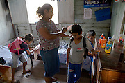 Solange Da Silva Correia helps her grandchildren get ready for school in their bedroom of her riverside home near the town of Caviana in Amazonas, Brazil. (Solange Da Silva Correia is featured in the book What I Eat: Around the World in 80 Diets.) The children load up their backpacks and use one of the family's outboard canoes to get to school in nearby Caviana, 20 minutes downriver.