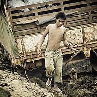Crew works to free mired transport truck in Mondulkiri Province, Cambodia