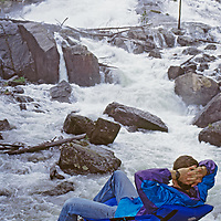 Hiker relaxes by cascades in Crazy Creek, in Absaroka Mountains near Yellowstone in Wyoming.