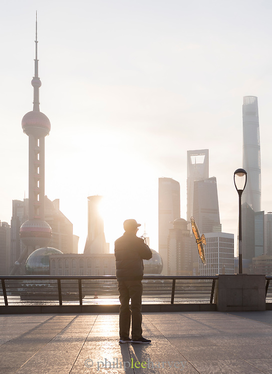 Senior man flying a kite and view of the futuristic Pudong skyline at sunrise, The Bund, Shanghai, China
