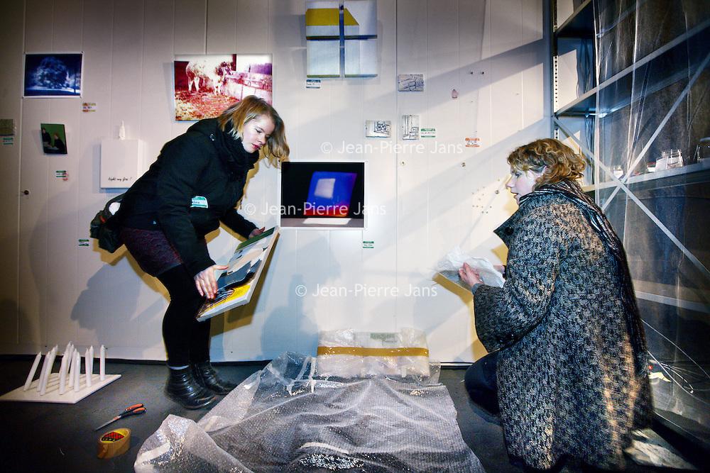 Nederland, Amsterdam, 2 december 2012..Kunstruilbeurs in Mediamatic aan de VOC kade..Voor alweer de elfde keer wordt de FITAX in Europa georganiseerd, dit keer samen met Mediamatic. De FITAX 500 is een kunst ruilbeurs waar kunstenaars en verzamelaars een werk met een waarde van ongeveer ?500 kunnen ruilen, zonder tussenkomst van geld. De uitgelezen kans om je collectie te vernieuwen of juist te starten. .Op de foto Celine van den Boorn (r) en Eveline Braak ruilen kunst met elkaar..Foto:Jean-Pierre Jans