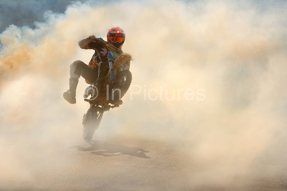 Man dangerously doing a wheelie on his motorbike through the smoke created from the springtime burning of the grass verges on the roadside in Narbonne, France.