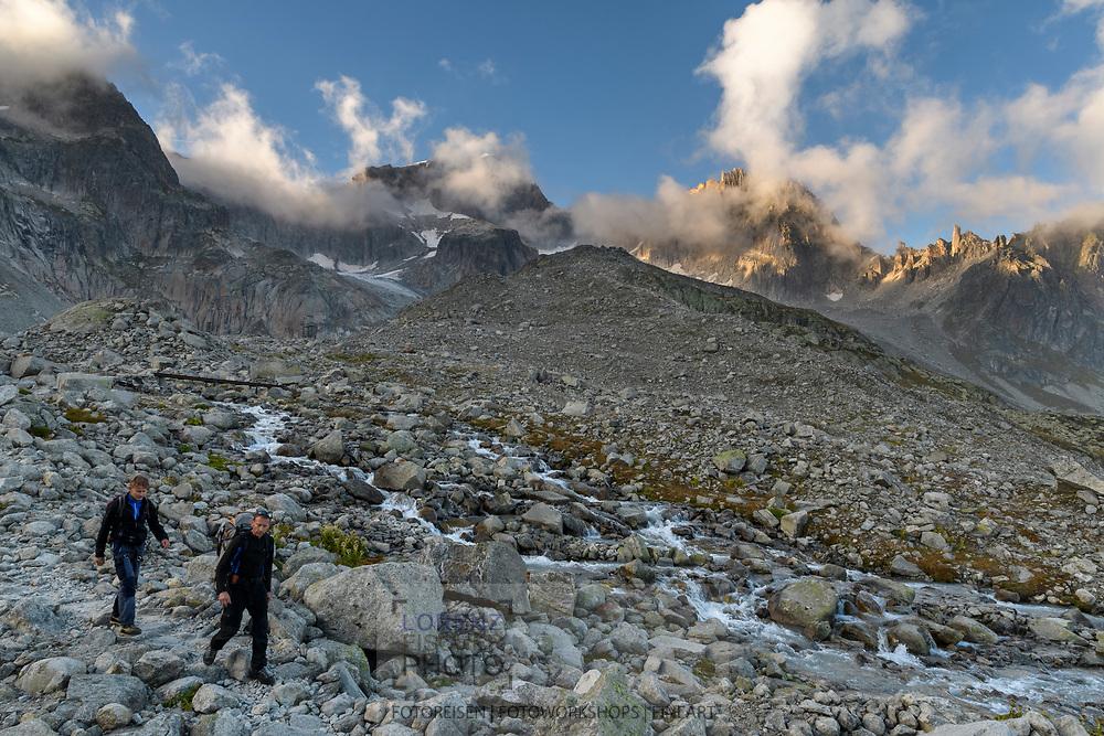 Zwei Alpinisten beim Abstieg auf dem Wanderweg. Im Hintergrund die Südwand des Galenstocks, das Gross Bielenhorn und das Kamel, Furka, Uri, Schweiz<br /> <br /> Two alpinists are hiking back on a trail. In the background the south face of Galenstock, Gross Bielenhorn and Kamel, Furka, Uri, Switzerland