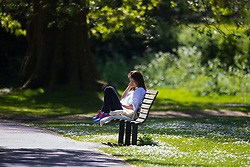A young woman soaks up the sun on a bench on a perfect spring day in Regents Park. London, May 04 2018.