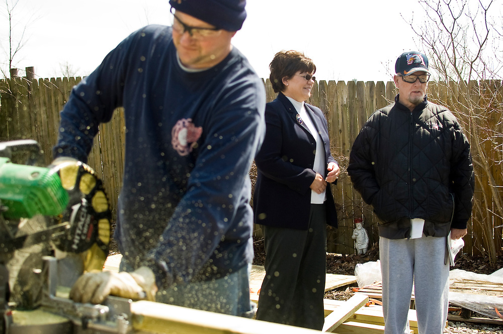 Matt Dixon | The Flint Journal..Burton Mayor Paula Zelenko (center) stopped by to chat with Army Veteran Charles Burnett (right) while Battalion Chief Kirk Wilkinson  (foreground) works to build a ramp outside Burnett's home in Burton Thursday afternoon. Local firefighters teamed up with Genesee County Habitat for Humanity for the project which was paid for by a grant from State Farm Insurance. Burnett, 77 was suggested by the Veterans Affairs Clinic in Flint to be a recipent.