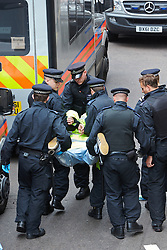 © Licensed to London News Pictures.  11/06/2013. LONDON, UK. An arrested anti G8 protester is carried by police officers.  Photo credit: Cliff Hide/LNP