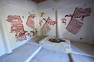 An exposed skeleton which were found in pits under the floors of some houses. On the wall are frescoes of what look like vultures, Scholars belive that dead bodies were subject to excarnation which means that their flesh was stripped from the body to leave the skeleton. A reconstruction of one of four Catalhoyuk houses to help archaeologists understand the finished structure of excavated ruins. 7500 BC to 5700 BC, Catalyhoyuk Archaeological Site, Çumra, Konya, Turkey .<br /> <br /> If you prefer to buy from our ALAMY PHOTO LIBRARY  Collection visit : https://www.alamy.com/portfolio/paul-williams-funkystock/catalhoyuk-site-turkey.html<br /> <br /> Visit our TURKEY PHOTO COLLECTIONS for more photos to download or buy as wall art prints https://funkystock.photoshelter.com/gallery-collection/3f-Pictures-of-Turkey-Turkey-Photos-Images-Fotos/C0000U.hJWkZxAbg