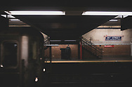 New York City, USA - March 18, 2020: A solitary man wearing a protective face mask stands on the platform at 181st Street Station in Manhattan.