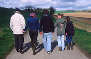 ADFTJ7 Back view of three generations extended family holding hands on country walk