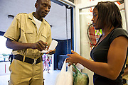 A security guard checks diamond polisher Mestilde Shigwedha's grocery items against her receipt at a supermarket in Windhoek, Namibia. Guards check the groceries of all shoppers to prevent shoplifting.