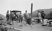 """""""trout caught in Walker Lake. Top & Smithy. 1912"""" Group of men on camping trip with car, portable wood stove, catch of fish, tents. (This image was selected as the poster image for the E. F. Box exhibition)"""