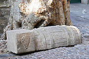 A stone sculpture on an old cobble stone street depicting a wine barrel and a grape bunch in Avignon, Vaucluse, Rhone, Provence, France