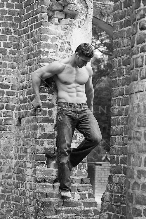 shirtless muscular man in jeans against a brick wall at an abandoned church in South Carolina