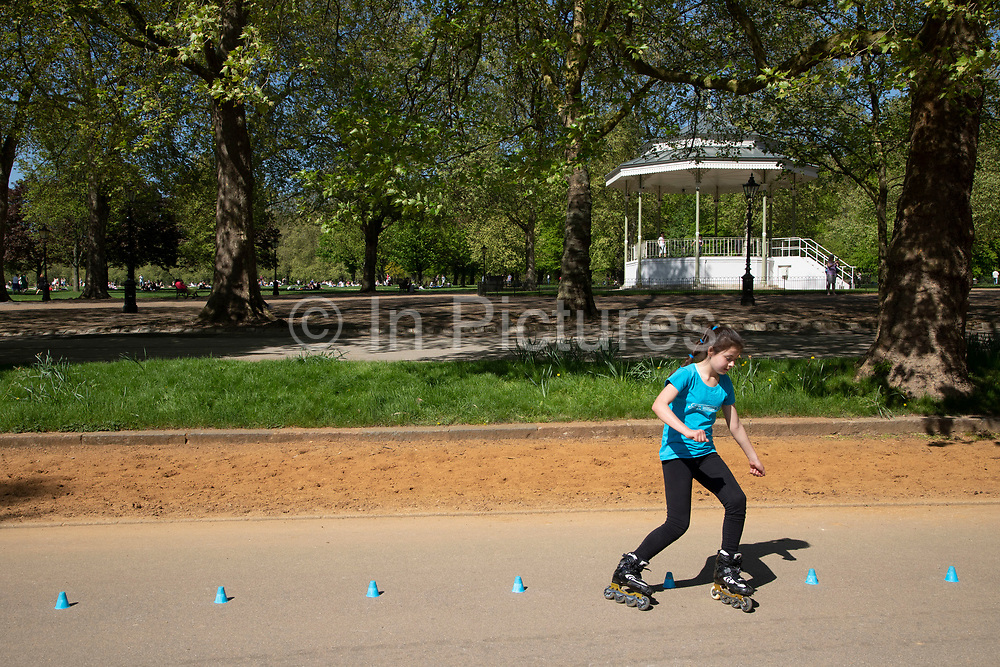 Young girl practices her slalom inline skating technique in Hyde Park in London, England, United Kingdom. People gather to walk along the promenade which is a popular place for rollerskating and rollerblading.