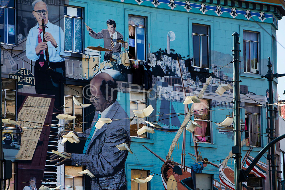 Mural painted on blue wall of large building showing jazz musicians, flying books and the bay area in San Francisco