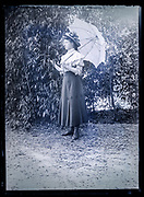stylish dressed woman standing in garden outdoors setting France ca 1920s