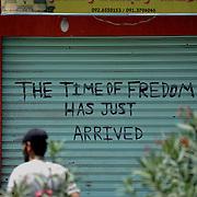 A local rebel fighter passes by a anti-regime graffiti in central Zawiya.