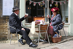 © Licensed to London News Pictures. 13/05/2016. Haworth, UK. A man and woman in 1940s enjoy cups of tea on the cobbled street during the annual 1940's weekend in Haworth, West Yorkshire.  Photo credit : Ian Hinchliffe/LNP