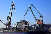 cranes at work loading unloading ship in port of Antwerp