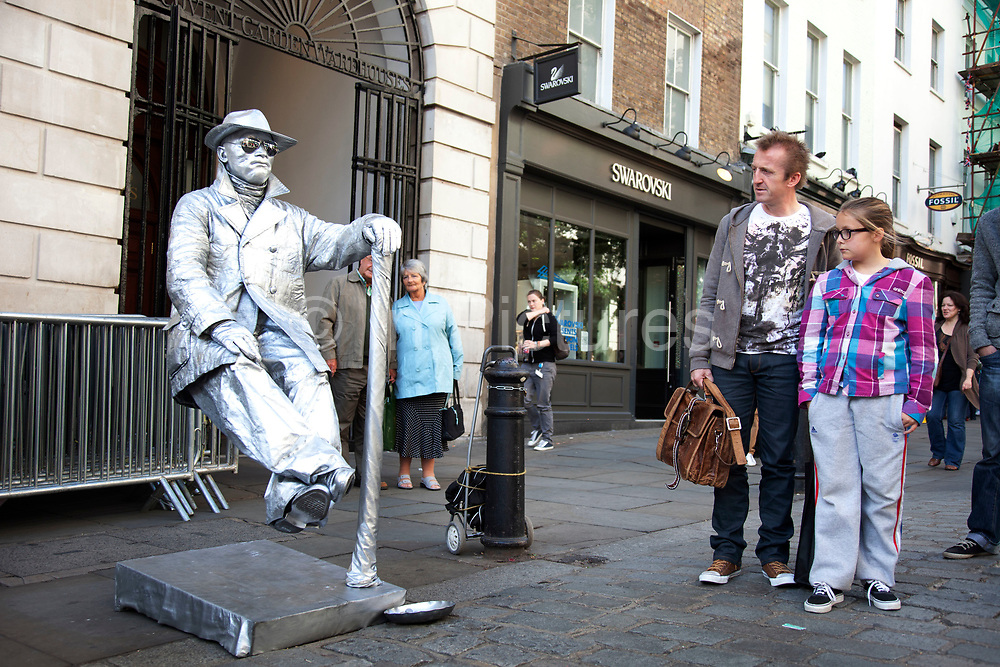 Statue street performer sits totally still as if floating in mid air in Covent Garden, in London, UK. There are many such performers making money in this way and having to increasingly be inventive in their guises.